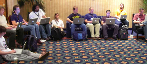 Geeks sitting with their Mac laptops at RailsConf 2006