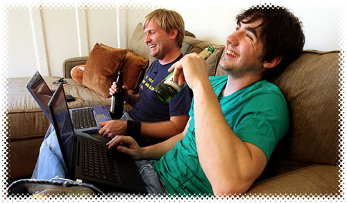 Alex Albrecht and Kevin Rose sitting on a couch with their laptops, drinking beer.