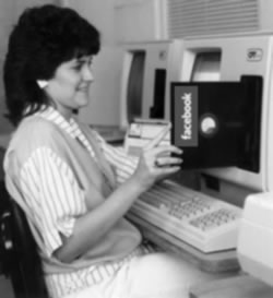 Woman at vintage computer with 8-inch floppy disk Photoshopped to have a Facebook label