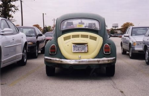 "Old VW Beetle with the licence plate that reads ""FEATURE""."