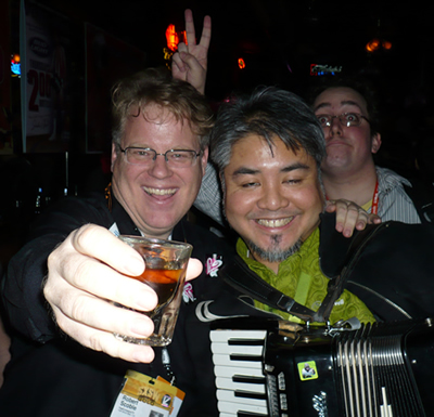 Robert Scoble (holding a shotglass) and a drunk Joey deVilla (holding an accordion)